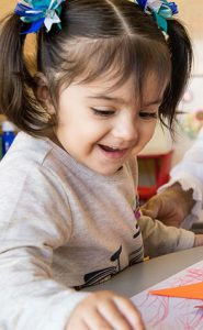 young hispanic child coloring a coloring book